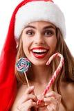 愉快的女孩有红色嘴唇的和圣诞节帽子的举行两圣诞节棒棒糖和微笑 查出 库存照片