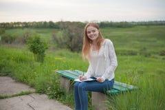 愉快的女孩欧洲出现坐与笔记本和笔的长凳 库存照片