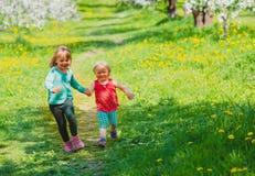 愉快的女孩演奏在春天自然,苹果开花,季节性活动的奔跑 免版税库存图片