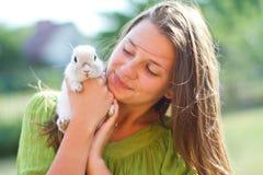愉快的女孩用在她的胳膊的一只兔子 免版税图库摄影