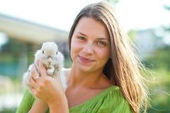 愉快的女孩用在她的胳膊的一只兔子 免版税库存图片