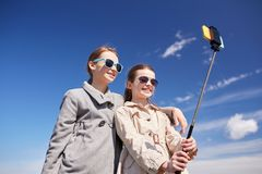 愉快的女孩用智能手机selfie棍子 免版税库存图片