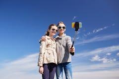 愉快的女孩用智能手机selfie棍子 免版税库存照片