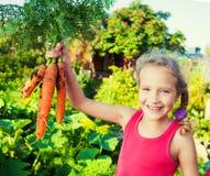 愉快的女孩用红萝卜 免版税库存照片