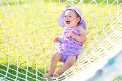 愉快的女孩画象在度假 反对吊床背景,一个小女孩在紫色褶坐 少许 免版税图库摄影