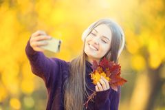 愉快的女孩画象有耳机的和智能手机在秋天停放听的音乐或做selfie 免版税库存图片