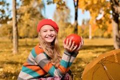 愉快的女孩秋天画象红色帽子和毛线衣的 免版税库存照片
