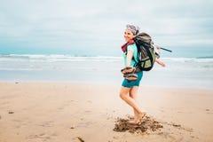 愉快的女孩背包徒步旅行者旅客在沙子海洋b赤足跑 免版税库存图片