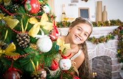 愉快的女孩装饰圣诞树 免版税库存图片