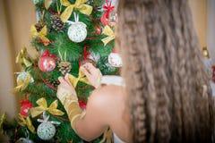愉快的女孩装饰圣诞树 图库摄影