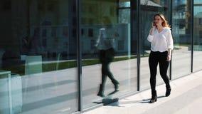 愉快的女孩谈话在智能手机,步行沿着向下街道在办公室中心附近 在事务打扮的妇女 股票视频