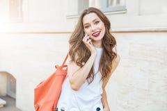 愉快的女孩谈话在站立的电话户外 免版税库存照片