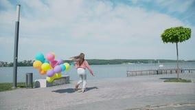 愉快的女孩走与在湖的岸的五颜六色的气球 4K 影视素材