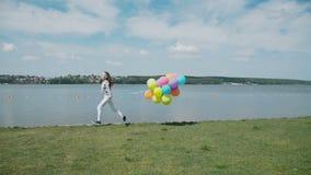 愉快的女孩跑与在夏天海湾的五颜六色的球 股票录像