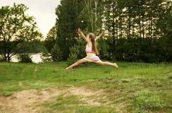 愉快的女孩跳到天空在黄色草甸在日落 免版税库存图片