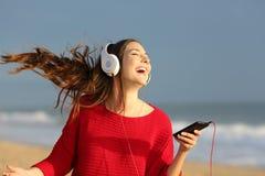 愉快的女孩跳舞和听的音乐 免版税库存图片