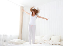 愉快的女孩跳跃和获得乐趣在床上 免版税图库摄影