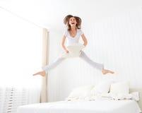 愉快的女孩跳跃和获得乐趣在床上 库存图片