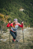 愉快的女孩运动员攀登与北欧人走的杆的一座山 图库摄影