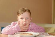 愉快的女孩食用一顿快餐在厨房 一个逗人喜爱的小女孩微笑 有巧克力奶油的一个小女孩在面孔弄脏 库存图片
