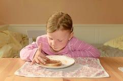 愉快的女孩食用一顿快餐在厨房 一个逗人喜爱的小女孩微笑 有巧克力奶油的一个小女孩在面孔弄脏 免版税库存照片