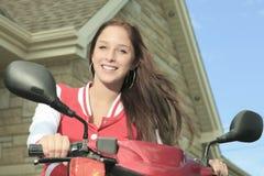 愉快的女孩骑马滑行车享受暑假 库存图片