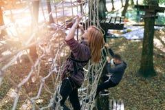 愉快的女孩,妇女,在冒险的上升的齿轮,绳索路,保险,吸引力,游乐场,活跃休闲,秋天 免版税库存图片
