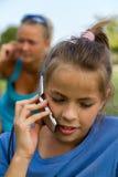 愉快的女孩,当讲话与移动电话时 库存照片