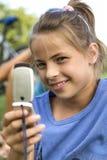 愉快的女孩,当讲话与移动电话时 免版税库存图片