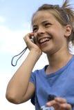 愉快的女孩,当讲话与移动电话时 图库摄影