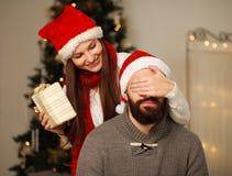 愉快的女孩给她的男朋友一个圣诞节礼物 免版税库存图片