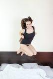愉快的女孩以成功的名义跳在卧室 库存图片