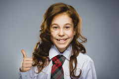 愉快的女孩 特写镜头画象英俊青少年在偶然在灰色背景的衬衣微笑的展示赞许 免版税库存照片