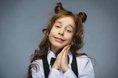 愉快的女孩 特写镜头画象英俊青少年恳求或beging在灰色背景 免版税库存照片