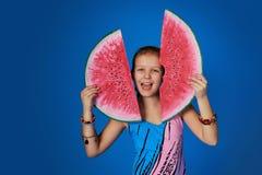 愉快的女孩画象拿着切片在五颜六色的蓝色背景的西瓜的泳装的 免版税库存图片