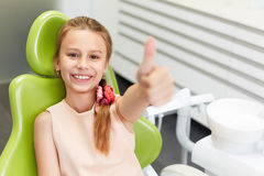 愉快的女孩画象显示赞许姿态在牙齿诊所 免版税库存图片