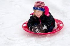 愉快的女孩sledding与一个红色茶碟雪撬 免版税图库摄影
