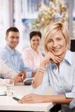 愉快的女实业家在会议室里 免版税库存照片
