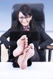 愉快的女实业家放松在海滩 库存图片
