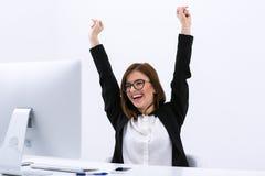 愉快的女实业家用被举的手 免版税图库摄影