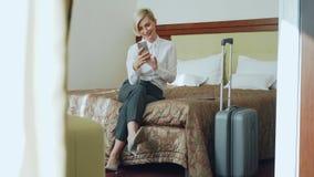 愉快的女实业家谈话与家庭通过网上录影闲谈使用smrtphone照相机坐床在旅馆客房 股票录像