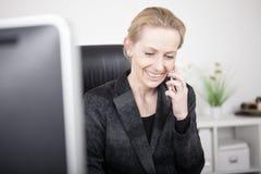 愉快的女实业家谈话与某人电话的 库存图片