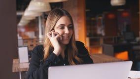 愉快的女实业家谈话在有坐在咖啡馆的伙伴的电话 股票视频