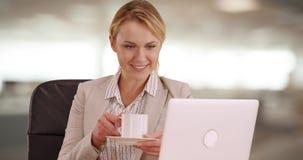 愉快的女实业家饮用的咖啡在工作 库存图片