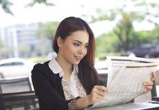 愉快的女实业家读书报纸和微笑 库存图片