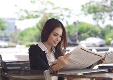 愉快的女实业家读书报纸和微笑 免版税库存图片