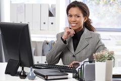 愉快的女实业家画象书桌的 免版税库存图片