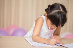 愉快的女小学生在她的家庭作业工作 免版税库存照片