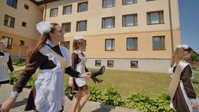 愉快的女小学生毕业生沿街道走 俄国毕业生庆祝最后教学日 影视素材