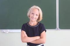 愉快的女小学生画象9-11岁在黑板附近的一间教室 回到学校 免版税库存照片